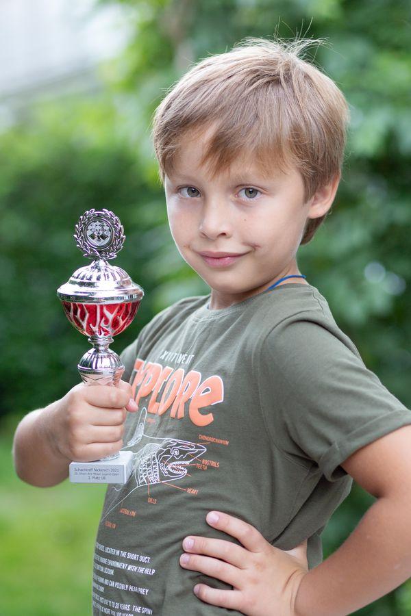 Maksim zeigt stolz seinen ersten Schachpokal